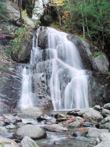 Wasserfall fließt über Steine Poster